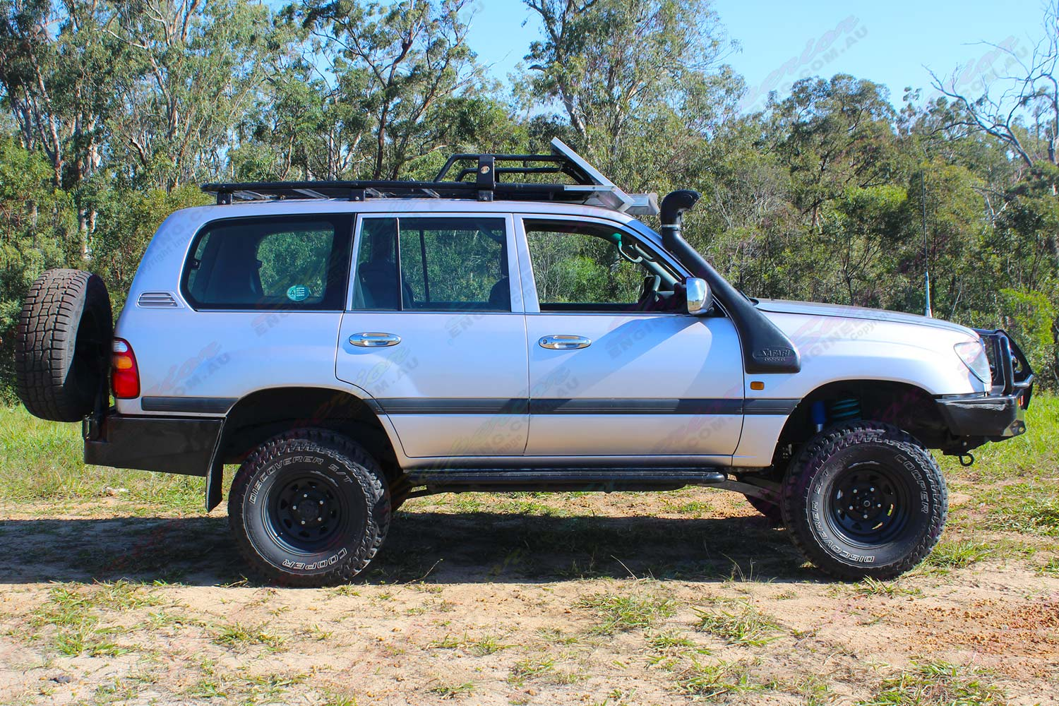 Right side view of a 105 Series Toyota Landcruiser wagon after being fitted with a heavy duty dobinsons coil springs, Superior nitro gas shocks and steering damper