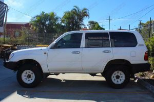 Left side view of a white 100 Series Toyota Landcruiser after being fitted with a heavy duty 2 inch Superior nitro gas lift kit