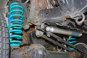 Closeup view of a Superior nitro gas steering damper and coil spring fitted to the front of the 100 Series Toyota Landcruiser 4x4