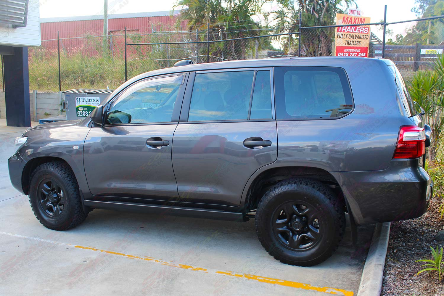 Left side view of a dark grey 200 Series Toyota Landcruiser 4wd fitted with a set of heavy duty Superior Engineering stealth rock sliders