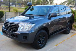 Front left side view of a dark grey 200 Series Toyota Landcruiser (with KDSS) fitted with a set of heavy duty Superior Engineering stealth rock sliders