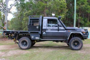 Right side view of a dark grey 79 series Toyota Landcruiser (single cab) ute after being fitted with a Superior Remote Reservoir Superflex 5 Inch Lift Kit