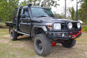 Front right angle view of a dark grey 79 series Toyota Landcruiser (single cab) after being fitted with a Superior Remote Reservoir Superflex 5 Inch Lift Kit