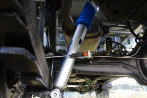Closeup under vehicle view of a Superior nitro gas shock absorber fitted to the 79 Series Toyota Landcruiser