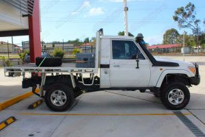 Right side view of a white 79 series Toyota Landcruiser (single cab) ute after being fitted with a Superior Remote Reservoir Superflex 4 Inch Lift Kit