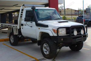 Front right view of a white 79 series Toyota Landcruiser (single cab) after being fitted with a Superior Remote Reservoir Superflex 4 Inch Lift Kit