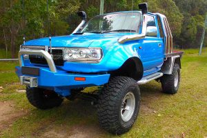 Front left side view of the blue single cab 80 Series Toyota Landcruiser after being fitted with a premium Superior Remote Reservoir 5 Inch Lift Kit