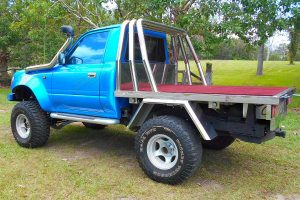 Rear left end view of the blue single cab 80 Series Toyota Landcruiser after fitting a Superior and Profender Remote Reservoir 5 Inch Lift Kit