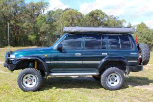 Left side view of a green 80 Series Toyota Landcruiser wagon fitted with dobinsons 4x4 4 inch coil springs and 6 inch shocks
