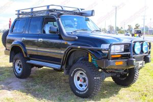 Front right side view of the green 80 Series Toyota Landcruiser wagon fitted with dobinsons 4 inch coil springs and 6 inch shocks plus superior rear lower control arms