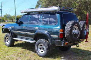 Left rear end view of the green 80 Series Toyota Landcruiser wagon fitted with dobinsons 4 inch coil springs and 6 inch shocks