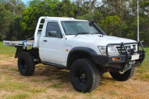 Front right view of a white Nissan Patrol GU Ute fitted with the heavy duty 4 inch Nitro Gas suspension kit from Superior