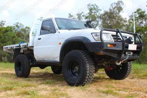 Front right low angle view of a white Nissan Patrol GU Ute fitted with the heavy duty 4 inch Nitro Gas suspension kit
