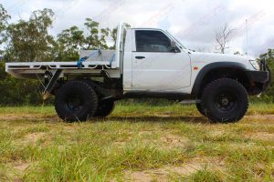 Right side low angle view of a white Nissan Patrol GU Ute fitted with the heavy duty 4 inch Nitro Gas suspension kit