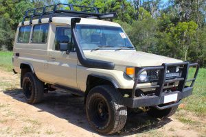 Front right view of a Toyota Landcruiser Troopy HJ75 after being fitted with a heavy duty 2 inch EFS lift kit and a Safari Snorkel