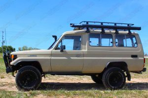 Left side view of a tan Toyota Landcruiser Troop Carrier HJ75 after being fitted with a heavy duty 2 inch EFS lift kit