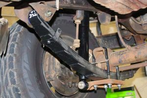 Closeup under vehicle view of a EFS leaf spring, u-bolts and shock fitted to the Toyota Landcruiser Troopy HJ75