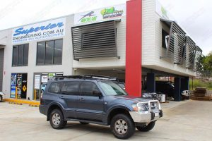 Front right view of a dark grey NP Mitsubishi Pajero fitted out with a 40mm Ironman lift kit out front of the Superior 4x4 showroom