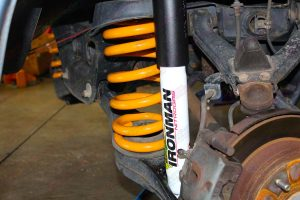 Closeup view of the Ironman Nitro gas shock and coil spring fitted to the underside of the Pajero