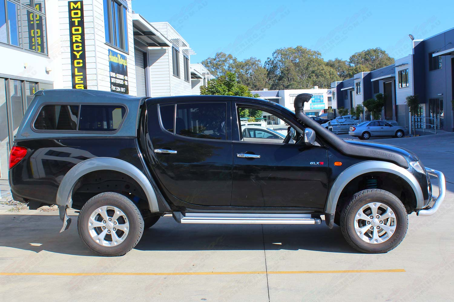 Right side view of a black ML Mitsubishi Triton (Dual Cab) fitted with an Ironman Bullbar and Snorkel, Superior Shocks and Dobinsons Springs