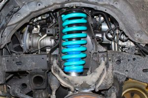 Closeup view of a Dobinson coil spring and Superior Nitro Gas Strut fitted to the front of a ML Triton