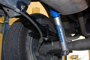 Closeup view of a Dobinson leaf spring and Superior Nitro Gas Shock fitted to the rear of a ML Triton