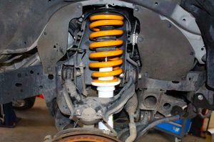 Closeup view of the Ironman 4x4 coil spring and foam cell strut fitted to the front of the ML Triton