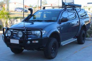 Front left view of a grey MN Mitsubishi Triton (Dual Cab) fitted with a 40mm Ironman lift kit and airforce snorkel