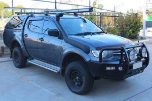 Front right view of a MN Triton (Dual Cab) fitted with a constant load 40mm Ironman lift kit and airforce snorkel