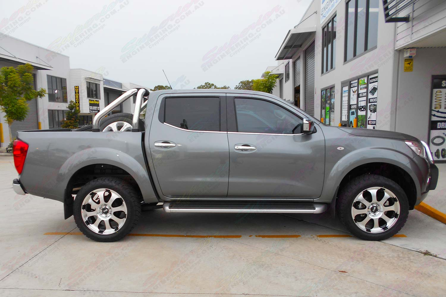 Left side view of a grey Nissan Navara NP300 after being fitted with a 35mm Ironman lift kit, Superior adjustable panhard rod, swaybar extensions & Advanti Hammer alloy wheels