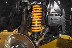 Closeup view of the Ironman 4x4 foam cell pro strut and coil spring fitted to the front underside of the NP300