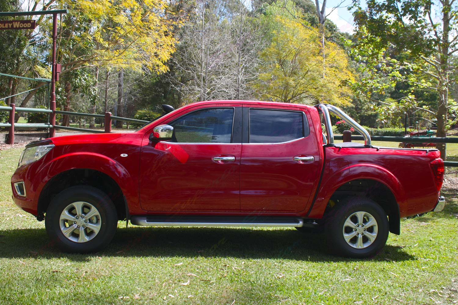 Left side view of a red Nissan Navara NP300 after being fitted with a 2 inch Dobinsons lift kit, TJM Airtec Snorkel and Superior Panhard Rod