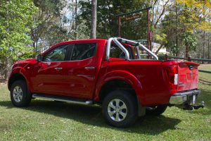 Rear left end view of the red NP300 Navara after being fitted with a 2 inch Dobinsons lift kit, TJM Airtec Snorkel and Superior Panhard Rod