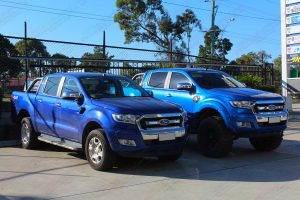 A Ford Ranger with factory suspension next to the Ford Ranger with a 5 inch lift kit at the front of the Superior 4wd retail store in Brisbane - Right Side View