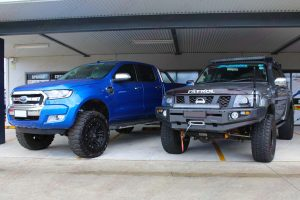 A 4 inch lifted Nissan Patrol next to the 5 inch lifted Ford Ranger at the front of the Superior 4wd retail store in Brisbane