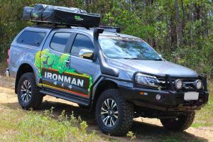 Front right view of an Ironman bullbar, snorkel, side steps, rails, roof tent and canopy fitted to a grey RG Holden Colorado dual cab four wheel drive vehicle