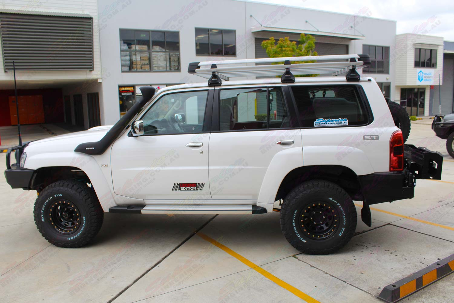 Left side view of a white Nissan Patrol Wagon after being fitted with a full custom suspension system and a range of 4x4 accessories by Superior Engineering
