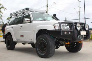Front right view of the white Nissan Patrol Wagon fitted with a full Superior suspension system and a range of 4x4 accessories at the front of the DBay 4WD Retail Store
