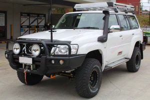 Front left view of the white Nissan Patrol Wagon fitted with a full Superior suspension system and a range of 4x4 accessories at the front of the DBay 4WD Retail Store