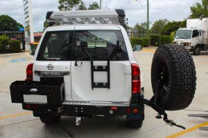 Rear end view of the Nissan Patrol fitted with MCC4x4 Rear bar with wheel carrier, dual jerry can carrier plus Superior Engineering Wheel Carrier with 2 x Lightforce ROK40 LED Lights