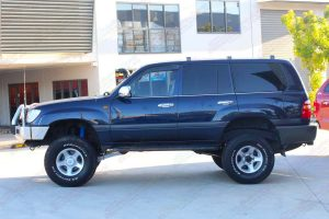 "Left side view of a blue 105 Series Toyota Landcruiser after being fitted with a top of the range 4"" inch lift kit"