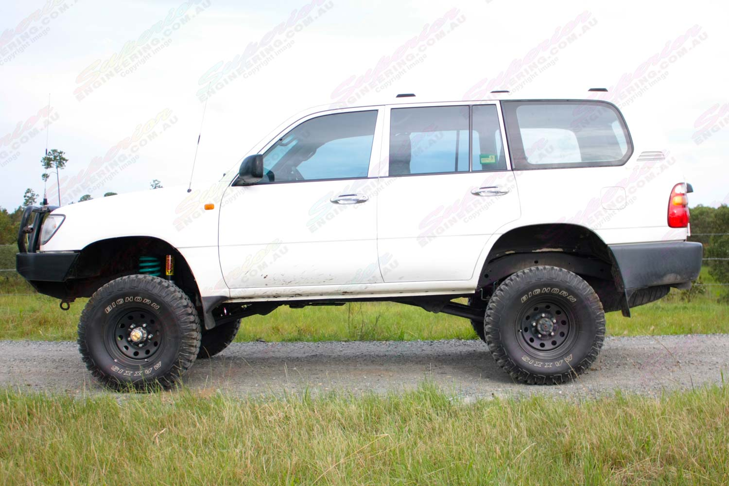 Left side view of a white 105 Series Toyota Landcruiser Wagon after being fitted with a 3 inch superflex lift kit featuring Tough Dog shocks