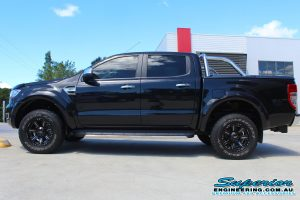 Left side view of a black PX Ford Ranger (Dual Cab) fitted with a 40mm Ironman 4x4 lift kit out the front of the Deception Bay 4WD retail store