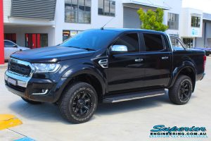 Front left view of a black PX Ford Ranger (Dual Cab) fitted with a 40mm Ironman 4x4 lift kit out the front of the Superior Engineering Deception Bay 4WD showroom
