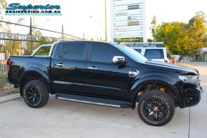 Right side view of a black PX Ford Ranger (Dual Cab) out the front of the Superior Engineering Deception Bay 4WD showroom after being fitted with an Ironman 4x4 40mm constant load lift kit