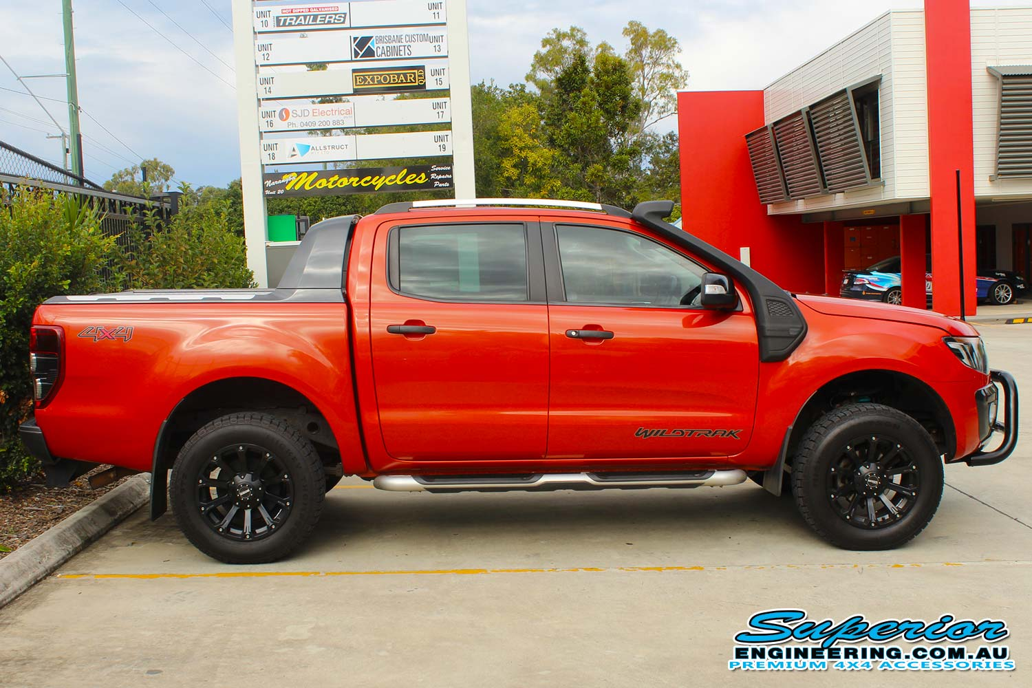 Right side view of an orange WildTrack Ford Ranger at the Deception Bay 4x4 Showroom fitted with a set of new Dobinsons coil springs