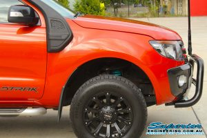 Closeup view of the front of an orange WildTrack Ford Ranger at the Deception Bay 4x4 Showroom fitted with a set of new Dobinsons coil springs