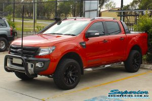 Front left view of an orange WildTrack Ford Ranger at the Deception Bay 4wd Retail Store fitted with a set of 40mm light duty Dobinsons coil springs