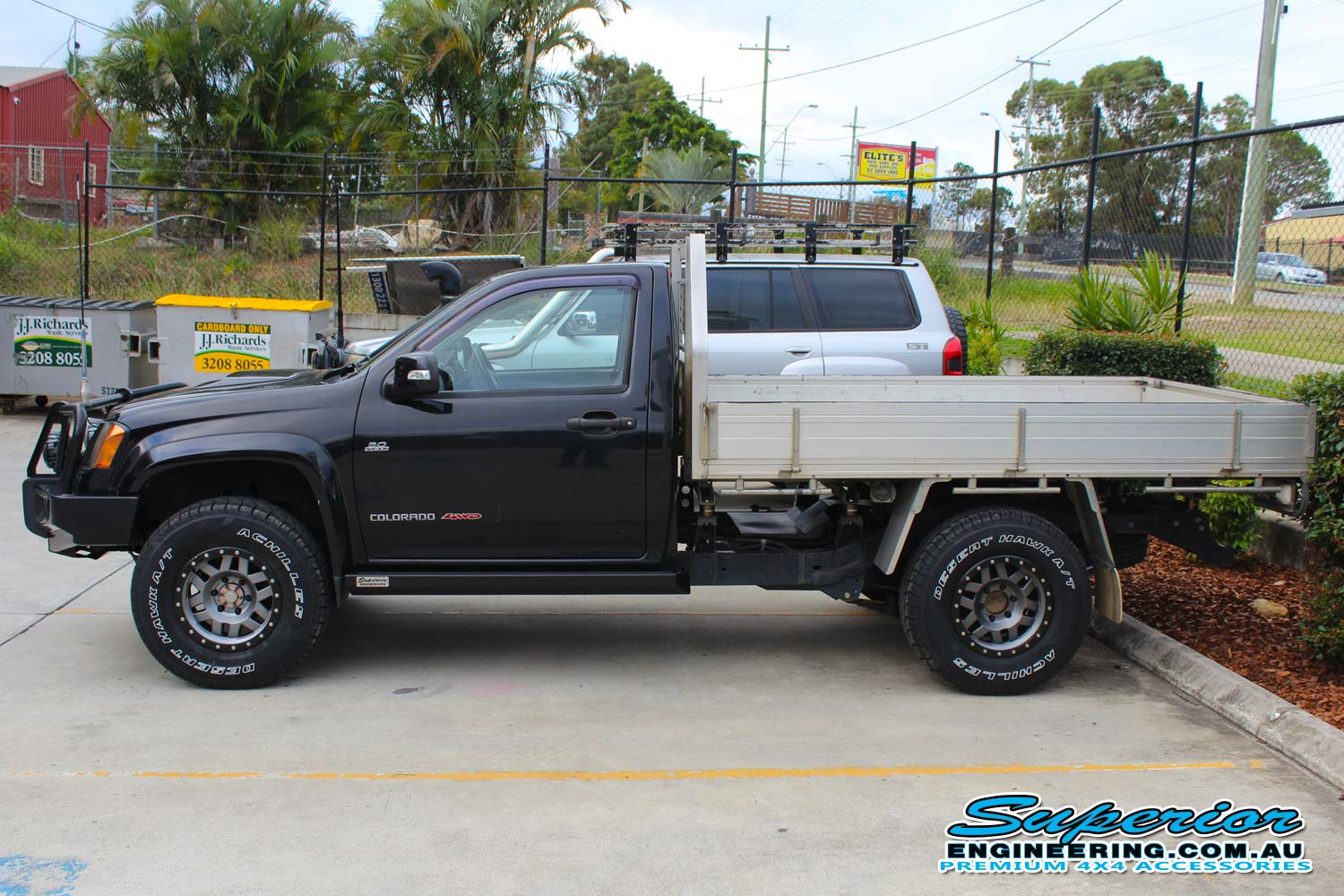 Left side view of a Black Single Cab RC Holden Colorado fitted with a 45mm Tough Dog lift kit, Superior stealth rock sliders, Ironman engine guard, Ironman monster winch, led spot lights and more