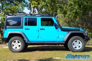 Right side view of a sky blue JK Jeep Wrangler Wagon fitted with a new Kaymar rear bar and spare tyre relocation kit